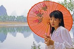 Young Chinese beauty with umbrella along Li River near Yangshuo in Guilin area