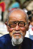 Bearded elderly Chinese man with broken antique eyeglasses at Xi'an's Huaqing Hot Springs park