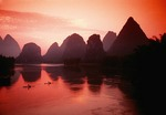 Li River with cormorant fishermen on bamboo rafts at dawn at Yangshuo in Guilin area