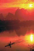 Li River with cormorant fisherman on bamboo raft at at sunset near Yangshuo in Guilin area