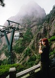 Tourist near one of three cable cars up summit of Huangshan (Yellow Mountain), this one near Jade Summit Terrace