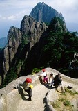 Chinese climbers at Huangshan (Yellow Mountain) pass a foreign photographer on steps up Lotus Flower Peak with Jade Screen Terrace and Celestial (Heavenly) Capital Peak in background