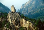 Huangshan's (Yellow Mountain's) Rock That Flew From Afar surrounded by climbers on clear day