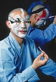 Beijing Opera performers applying grease paint makeup backstage