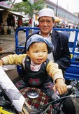 Hui Muslim man with his son on motorcycle in Lin Xia, Gansu province, a Silk Road town