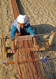 Elderly Turkmen woman weaving on loom in the desert along Silk Road in Turkmenistan in central Asia