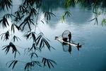 Li River near Xingping with fisherman through leaves of bamboo rowing on bamboo raft (Guilin/Yangshuo area of Guangxi)