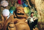 Tourist posing with Laughing Buddha carving in cave of Fubo (Wave-Subduing) Hill in Guilin