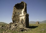 Remains of Church of the Redeemer St. Prkitch with Great Cathedral in background at Ani, ruined capital of Armenian Kingdom, on eastern Turkey border with Armenia