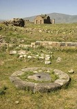 Remains of linseed oil press with Great Cathedral in distance at Ani, ruined capital of Armenian Kingdom, on eastern Turkey border with Armenia