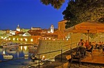 Dubrovnik Old Town outdoor cafe near Ploce Gate overlooking Old Port harbour in evening