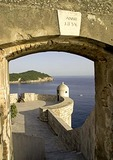 Dubrovnik Old Town's 1834 stone wall archway framing turret and Lokrum Island in Adriatic in background