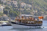 Dubrovnik tourist excursion ship entering Old Port after cruise around City Walls on Dalmatian Coast of Adriatic