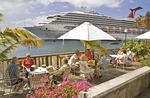Cruise passengers in Roseau relax at dockside cafe near their Carnival Cruise Lines ship Destiny