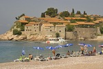 Beach at Sveti Stefan, exclusive island luxury resort hotel, with ferry arriving from Budva