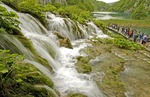 Plitvice Lakes National Park, waterfalls between lakes with young visitors on boardwalk