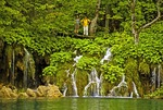 Plitvice Lakes National Park, waterfalls between lakes with visitors on boardwalk