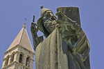 Split's Gregory of Nin statue by sculptor Ivan Mestrovic with tower of Diocletian's Palace
