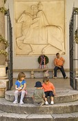 Trogir city centre children playing on steps near memorial carving of Petar Berislavic on horseback