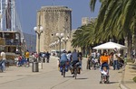 Trogir's palm-lined waterfront with Kamerlengo Fortress in background