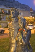Makarska waterfront promenade statue of strolling tourists in evening light