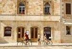 Hvar main town square with bicyclists on tour, on island of Hvar in Adriatic
