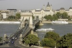 Budapest's Szechenyi Chain Bridge over Danube River looking toward Gresham Palace (Four Seasons Hotel) and St Stephen basilica in Pest