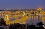 Budapest's Szechenyi Chain Bridge over Danube River looking toward Gresham Palace (Four Seasons Hotel) and St Stephen basilica in Pest at night