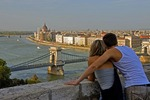 Budapest's Szechenyi Chain Bridge over Danube River with Parliament in background on Pest side with romantic couple on Buda Castle overlook