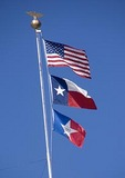 Flags of City of San Antonio, State of Texas, and USA (from bottom to top)