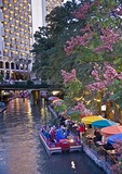 San Antonio Riverwalk river side Casa Rio Restaurant with Rio San Antonio Cruises dining cruise on San Antonio River in evening, Hilton Hotel in background