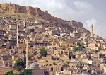 Mardin houses and minarets of old city below citadel-topped mountain