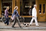 Amsterdam pedestrians passing Cafe van Zuylen on Torensteeg Street near Singel Canal