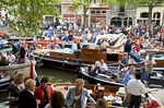 Amsterdam crowd in boats at free open air summer festival of classical music concerts on Prinsengracht Canal called Prinsengrachtenconcert or Grachtenfest