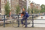 Amsterdam tourist with bike on bridge over canal