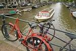 Amsterdam bikes locked to bridge with sightseeing cruise boat in Prinsengracht canal