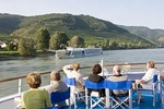 Danube River cruise ship passengers viewing MS Amadante cruising past scenic Wachau Valley village