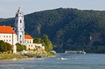 Durnstein village on Danube River with river cruise ship passing church, formerly an Augustinian monastery