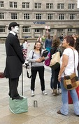 Cologne mime statue performer being viewed by tourist in cathedral square