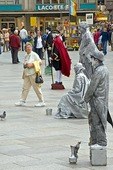 Cologne mime statue performers being viewed by tourist in cathedral square