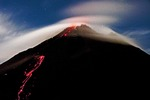 Arenal Volcano emitting smoking lava and incandescent pyroclastic flows at night