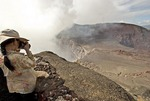 Masaya active shallow shield volcano, National Park visitor photographing from overlook of smoking crater