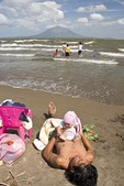 Lake Nicaragua beach at San Jorge with young father with baby, Concepcion volcano on Ometepe Island in background