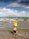 Lake Nicaragua beach at San Jorge with young man doing hand stand, Concepcion volcano on Ometepe Island in background