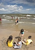 Lake Nicaragua beach at San Jorge with children playing, Concepcion volcano on Ometepe Island in background