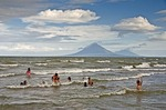 Lake Nicaragua beach north of Rivas with children playing with their teacher, Concepcion and Maderas volcanoes on Ometepe Island in background