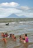 Lake Nicaragua beach north of Rivas with children playing game with their teacher, Concepcion and Maderas volcanoes on Ometepe Island in background
