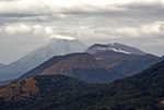 View from Cerro Negro volcano northwest past Telica and Casita volcanoes to smoking San Cristobal in chain of 25 volcanoes in Nicaragua