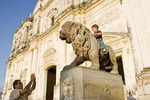 Leon Cathedral, Spanish colonial architecture, with Nicaraguan man photographing boy on lion statue flanking entrance
