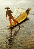 Inle Lake, Intha leg rower with fishing net on boat in late afternoon light